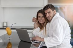 Young couple in bathrobe at home having coffee in the kitchen and working on laptop computer.  Stock Photo