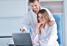 Young couple in bathrobe at home having coffee in the kitchen and working on laptop computer Stock Photos