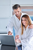 Young couple in bathrobe at home having coffee in the kitchen and working on laptop computer.  Royalty Free Stock Photos