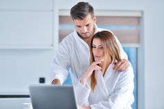 Young couple in bathrobe at home having coffee in the kitchen and working on laptop computer Stock Photo