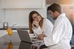 Young couple in bathrobe at home having coffee in the kitchen and working on laptop computer.  Royalty Free Stock Photography