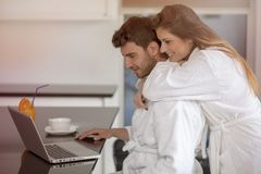 Young couple in bathrobe at home having coffee in the kitchen and working on laptop computer.  Stock Images