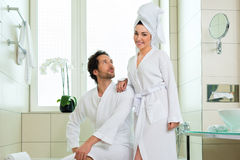 Young couple in bathrobe in hotel bathroom Royalty Free Stock Photos