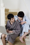 Young couple in bathrobe sitting on stairway with laptop Stock Images