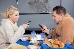 Young couple in bathrobes eating breakfast Royalty Free Stock Photo
