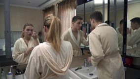 Young couple in the bathroom. Beautiful couple in dressing gowns in the bathroom. Attractive blonde is painting eyebrows. Handsome guy touches his hair stock video