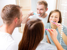 Young couple in the bathroom brushing teeth. Together Stock Image