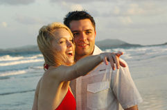 Young couple at the beach. Young couple a the beach going for an afternoon walk at the waters edge Royalty Free Stock Images