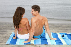 Young couple at the beach. Attractive young man and woman friends on a beach towel Royalty Free Stock Photography