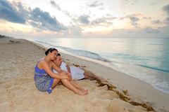 Young couple on the beach. Young couple watching sunrise on the beach Royalty Free Stock Photos