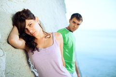 Young couple on the beach. Attractive coupe on the seaside lean against the rock Royalty Free Stock Photography