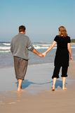 Young couple on the beach. Young married couple in love walking hand-in-hand on the beach during their winter vacation in South Africa royalty free stock photography