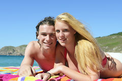 Young couple on the beach. Attractive boy and girl sunbathing on the beach Stock Photography