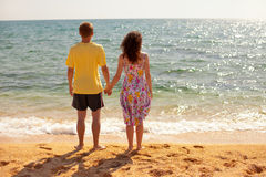 Young couple on the beach. Young couple holding hands staying on the beach back to camera and looking on the sea stock images