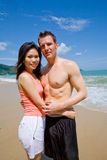 Young couple by the beach. Beautiful couple at the beach cuddling each other Royalty Free Stock Photo