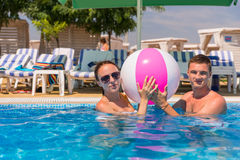 Young Couple with Beach Ball in Swimming Pool Royalty Free Stock Images