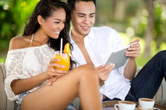 Young couple in beach bar using tablet Royalty Free Stock Photos