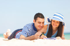 Young couple on the beach. Beautiful couple on the beach writing something Stock Photography