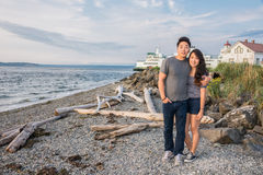 Young Couple on Beach with Ferry and Lighthouse. Young cute Asian American couple, men with arm around shoulder of woman, standing on beach. Ferry and lighthouse royalty free stock photo