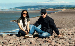 Young couple in the beach. Happy young couple in love relaxing in a  beach of Minehead, UK  enjoying ocean view together Stock Images