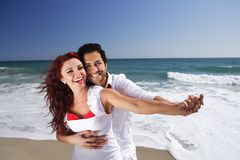 Young Couple at the beach holding hands Stock Image