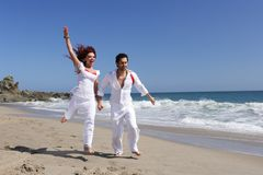 Young Couple at the beach jumping Stock Photography