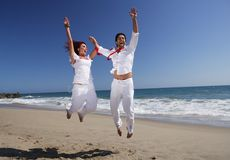 Young Couple at the beach jumping for joy Royalty Free Stock Photos