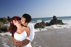 Young Couple at the beach kissing Stock Photo