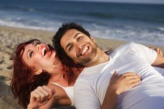 Young couple at the beach laughing Stock Photo