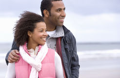 Young couple on beach, man with hand on woman's shoulder, smiling Stock Photos