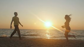 Young couple on the beach, man hug and spin around his woman on sunset. Girl jumps into her boyfriend arms, he whirling her at bea. Utiful seaside. Having fun stock footage