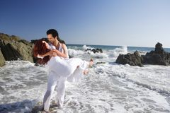 Young Couple at the beach playing in waves Royalty Free Stock Photo