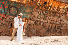 Young couple in a beach with shipwreck Royalty Free Stock Image