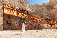 Young couple in a beach with shipwreck Royalty Free Stock Photo