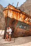 Young couple in a beach with shipwreck Stock Images