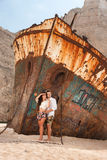 Young couple in a beach with shipwreck Royalty Free Stock Photography