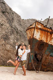 Young couple in a beach with shipwreck Royalty Free Stock Images