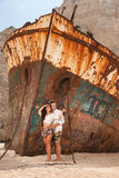 Young couple in a beach with shipwreck Stock Photos