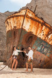 Young couple in a beach with shipwreck Stock Photography