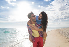 Young Couple On Beach Summer Vacation, Happy Smiling Man Carry Woman Back Seaside royalty free stock image