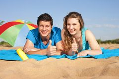 Young couple at the beach with thumbs up Stock Images