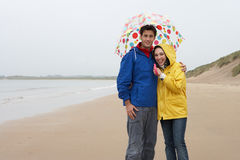 Young couple on beach with umbrella Royalty Free Stock Photography
