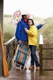 Young couple on beach with umbrella Royalty Free Stock Photos