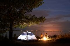 Young couple man and woman having rest at tourist tent and burning campfire on sea shore near forest. Young couple, bearded men and women hikers having a rest at stock photography