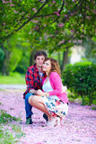 Young couple among beautiful sakura petals in spring garden Royalty Free Stock Photography
