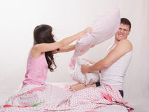 Young couple in bed arranged a pillow fight Royalty Free Stock Images