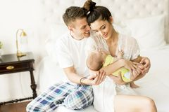 Young couple on the bed with baby girl. View at young couple on the bed with baby girl Stock Photos