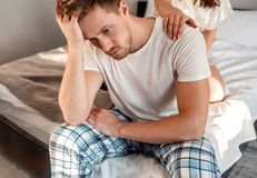 Young couple in the bed. Close-up of unhappy man is sitting on the edge of bed, problem in the bedroom stock photography