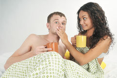 Young couple in bed with coffee Stock Photos