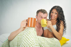 Young couple in bed with coffee Royalty Free Stock Photos